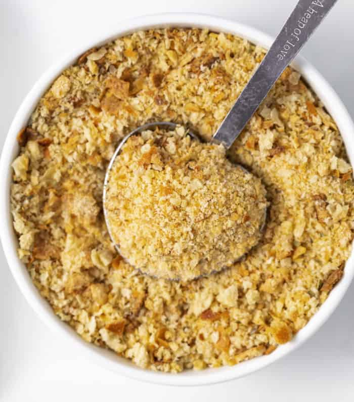 A tablespoon in a white bowl full of homemade breadcrumbs.