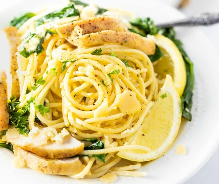 A white plate filled with Lemon Ricotta Parmesan Pasta with chicken, parsley, and a lemon wedge.