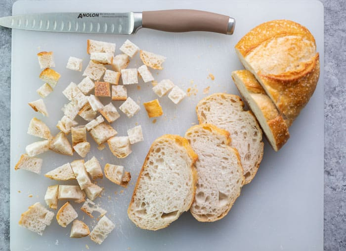 A loaf of Italian bread being cut into cubes on a white cutting board.