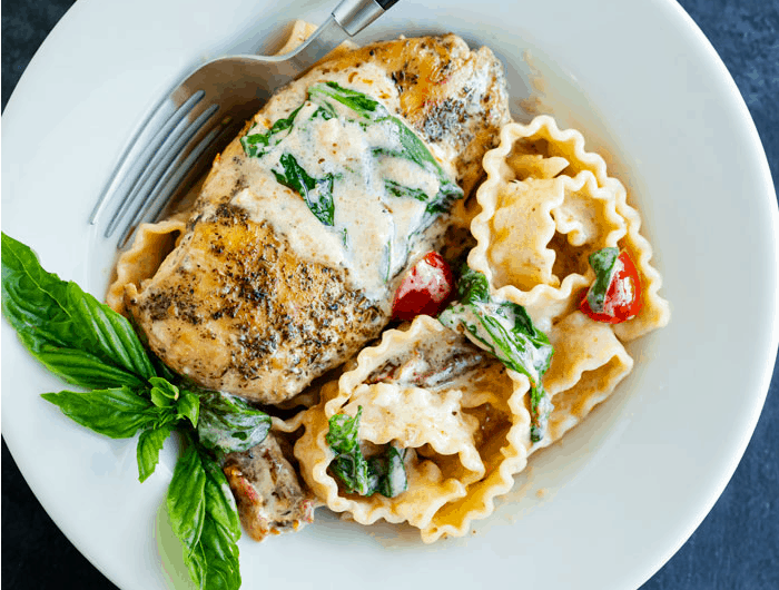 A white plate with a cooked chicken breast with sauce on top next to pasta noodles and fresh basil.