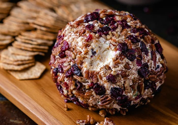 A pineapple pecan cheese ball on a wooden cutting board with crackers in the background.