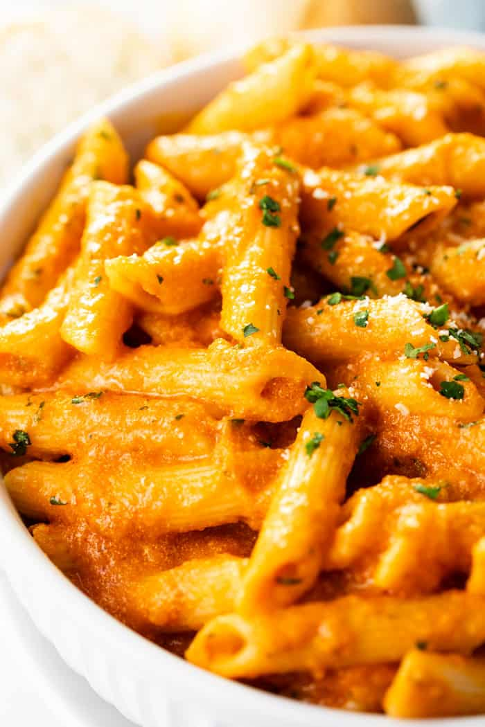 Close up view of penne alla vodka in a white bowl topped with parsley and Parmesan cheese.