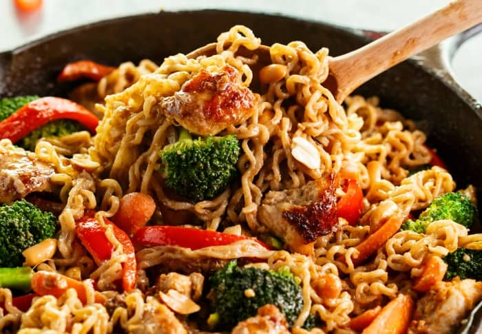 A cast iron skillet filled with vegetables, chicken, and ramen noodles in a peanut sauce with a wooden spoon scooping it up.