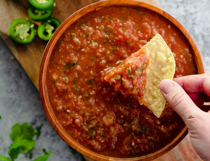 A bowl of salsa with a hand dipping a chip into it. Jalapenos are in the background.