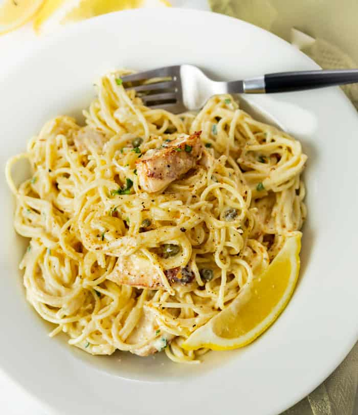 A white bowl filled with Chicken Caesar Pasta with chicken, capers, and lemons