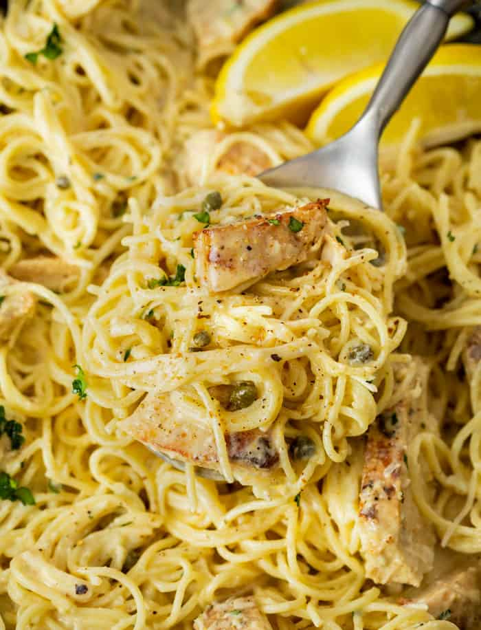 A spoon scooping up angel hair in a creamy Caesar sauce from a pot with capers and lemons.