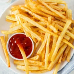 A white plate full of homemade McDonald's French Fries and kechup.