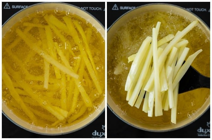 French fries in a dutch oven being fried at 300 degrees and then lifted from the oil with a slotted spoon.
