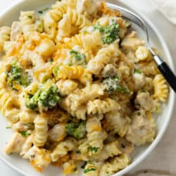 A white plate with Chicken Noodle Casserole with with a creamy mushroom cheese sauce and broccoli.