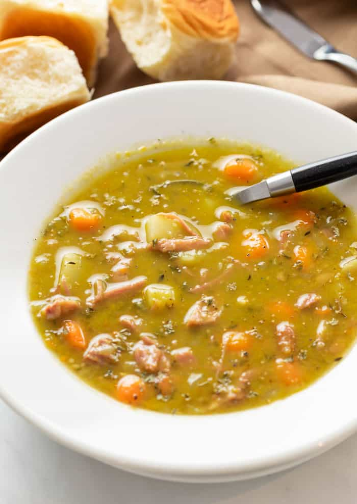 A white bowl with split pea soup in it filled with ham, carrots, and potatoes.