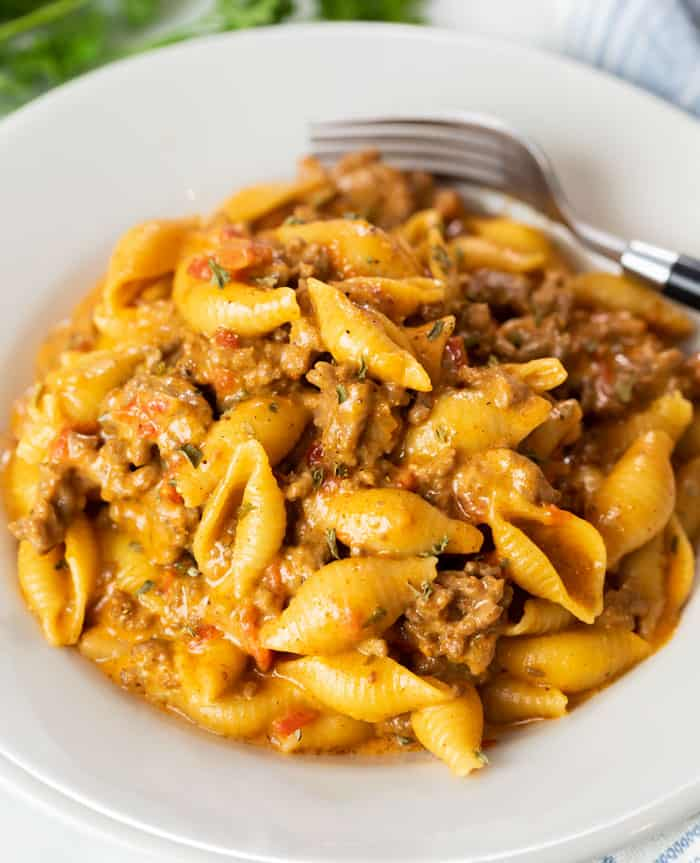 A white bowl filled with cheesy pasta shells and ground beef for Taco Pasta.