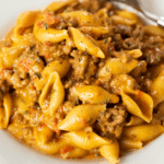 A pile of cooked pasta shells and beef in a taco pasta sauce.