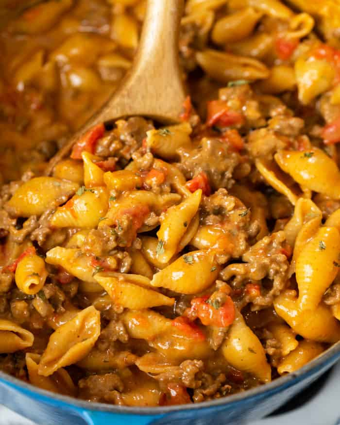 A skillet filled with cheesy pasta shells tossed with seasoned ground beef and tomatoes for taco pasta.