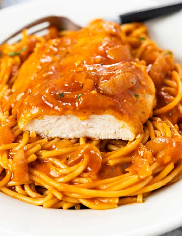 A slice of chicken breast on top of a plate of spaghetti in a red scallopini sauce.