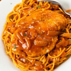 Chicken breast on top of a pile of spaghetti with a red chicken scallopini sauce with sliced onions and parsley.