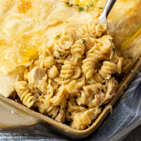 A scoop of French Onion Chicken Noodle Casserole being lifted from a casserole dish.