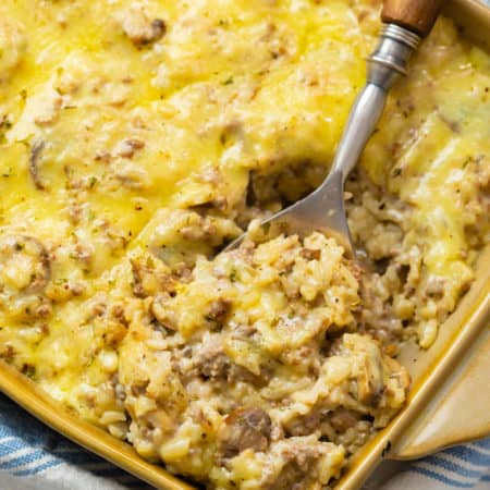 A casserole dish filled with cheesy ground beef and rice casserole.