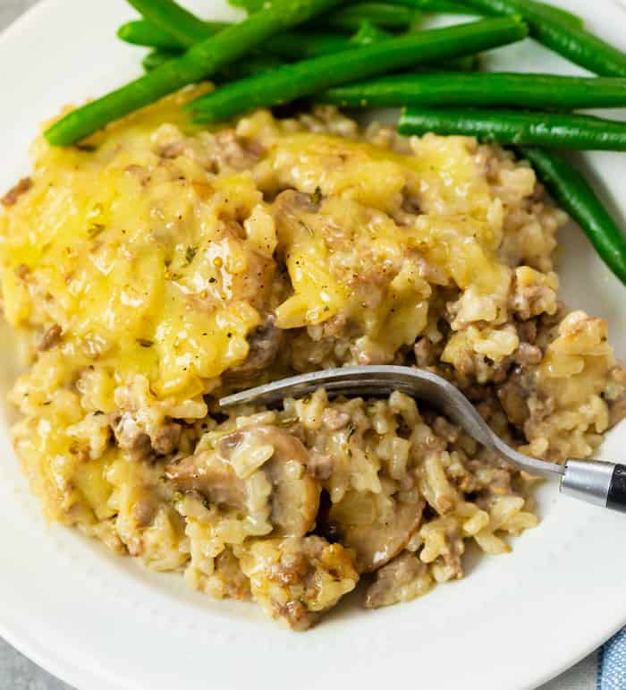 A white plate with cheesy ground beef and rice casserole with a fork. Green beans in the background.