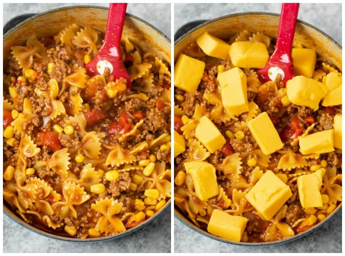 Cooked pasta noodles in sloppy joe sauce with cheese being added to make sloppy joe casserole