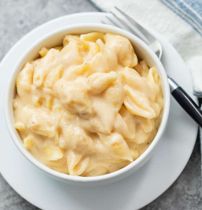 A white bowl of Panera mac and cheese on a white plate with a fork .