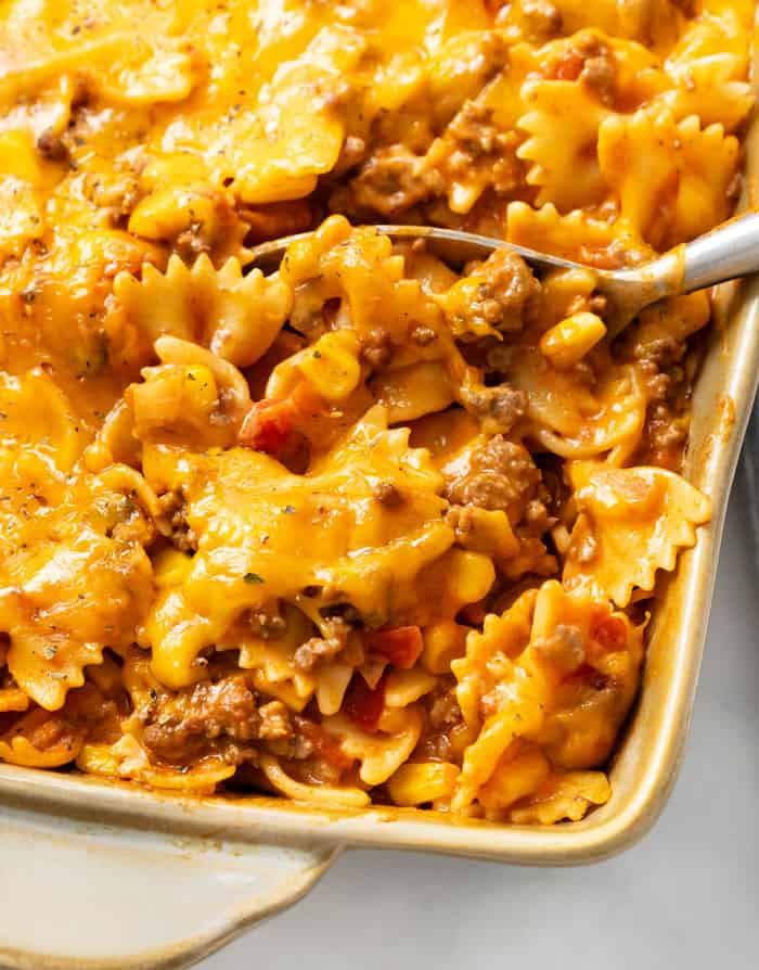 A spoon full of sloppy joe casserole in a casserole dish.