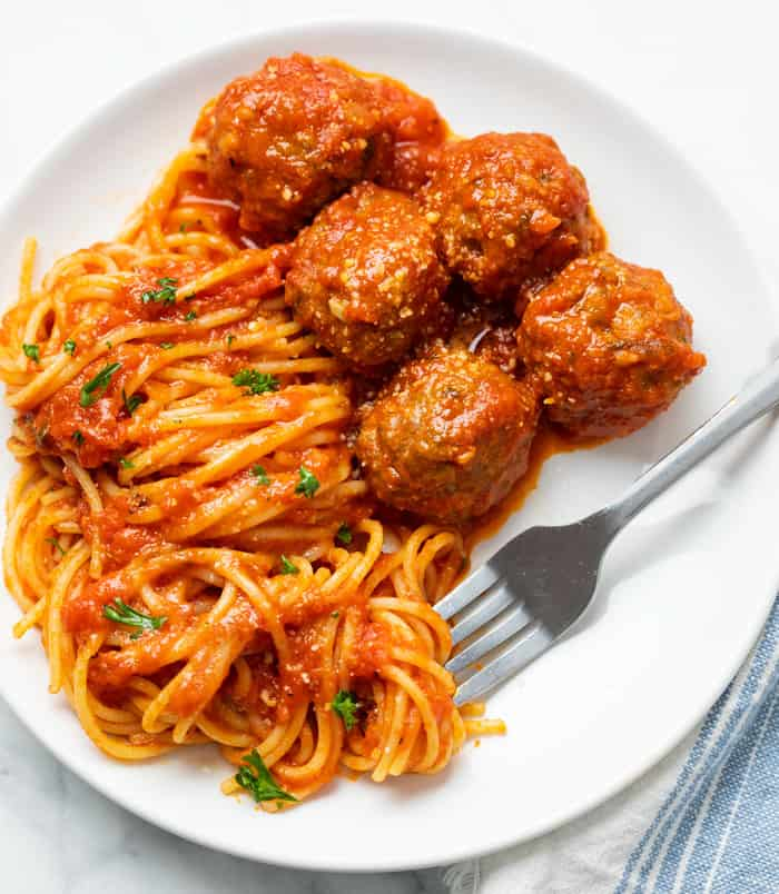 A white plate with spaghetti and slow cooker meatballs with a fork.