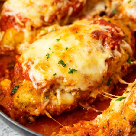 A breaded chicken breast topped with melted mozzarella in a pan with marinara sauce for Baked Chicken Parmesan.