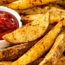 A pile of crispy baked potato wedges on a platter with ketchup on the side.