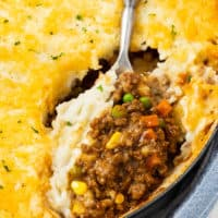 A large spoon scooping Shepherds Pie from a casserole dish.