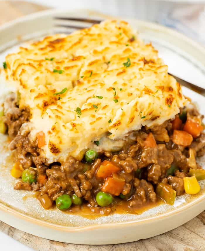 A plate with a slice of easy shepherds pie with ground beef with a fork in the background.