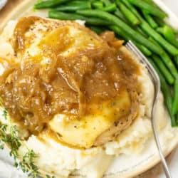 Seasoned chicken breast stopped with melted mozzarella cheese and French Onion Sauce on top of mashed potatoes on a plate with a fork.