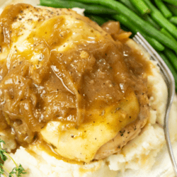 Chicken Breasts topped with melted mozzarella and a French Onion Sauce on top of mashed potatoes with green beans in the background.
