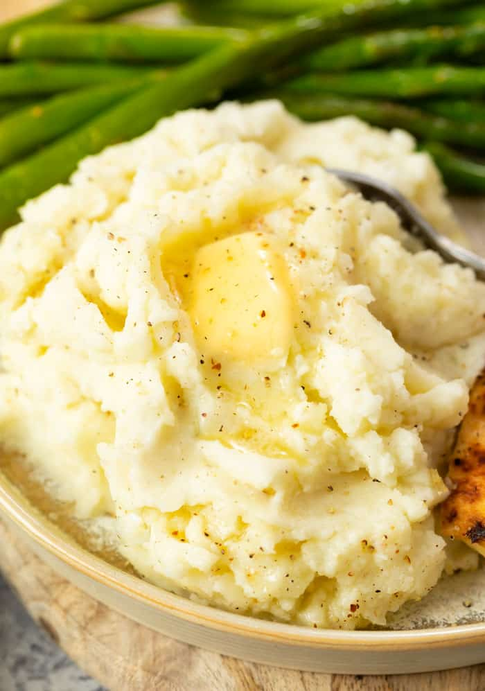 A plate with a pile of mashed poatoes with butter and cracker pepper on it with asparagus in the background.