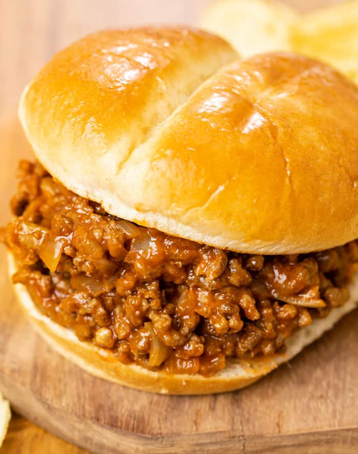 A burger bun filled with homemade sloppy joes on a wooden surface.