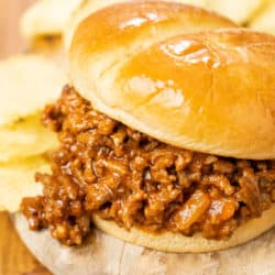 A hamburger bun filled with homemade sloppy joes on a wooden plate with chips in the background.