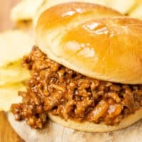 Homemade sloppy joes in a buttery hamburger roll with potato chips in the background.