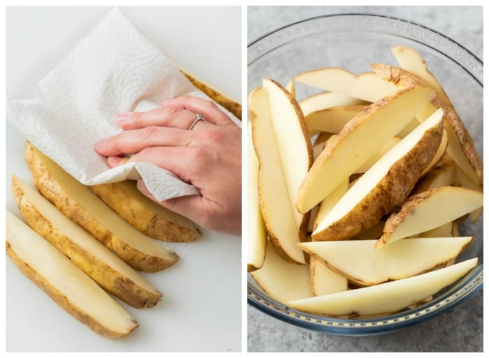 Unbaked potato wedges being patted dry and put in a bowl to be seasoned.
