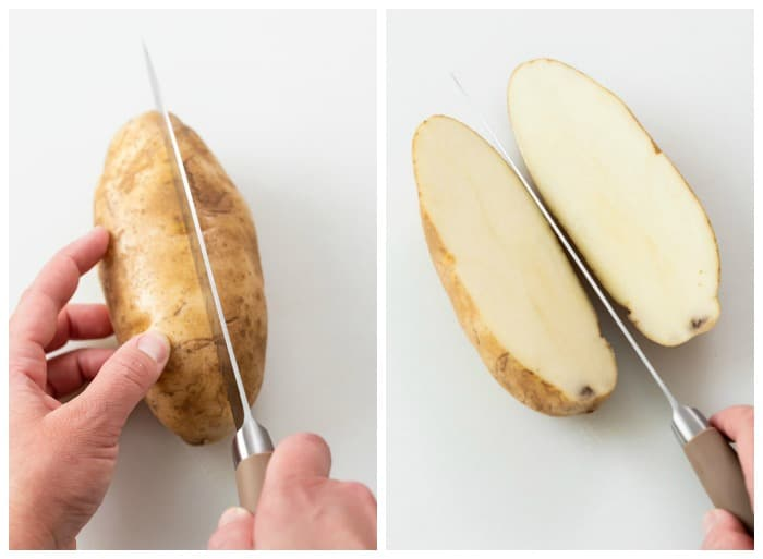A potato being sliced in half to make wedge potatoes.