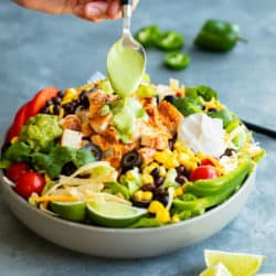 A bowl filled with Southwest Salad with a hand drizzling cilantro dressing on top.