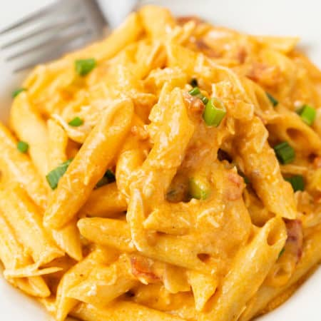 A white plate with buffalo chicken pasta with a fork in the background.