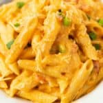 Penne pasta smothered in a creamy buffalo chicken sauce with green onions.