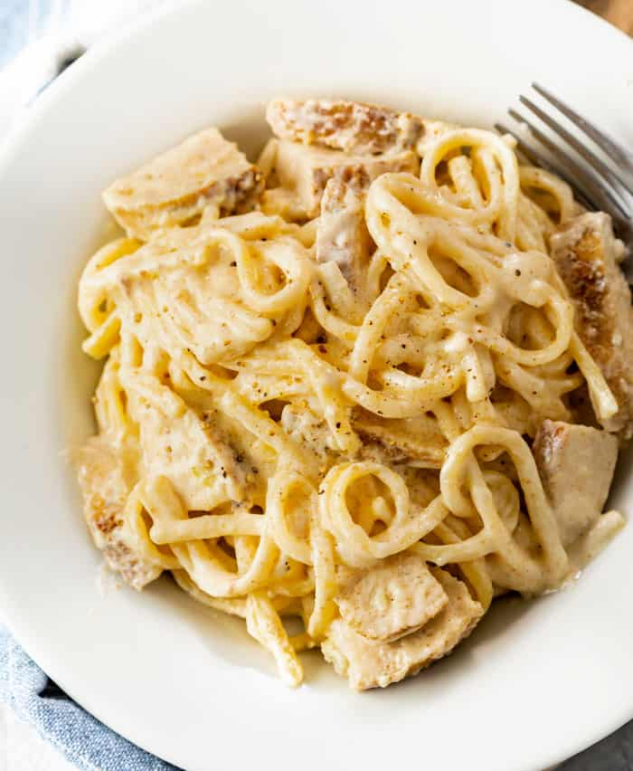 A white bowl filled with Cajun Chicken Pasta with fettuccine noodles and Alfredo sauce.
