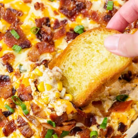 A hand holding a crusty piece of bread and dipping it into hot corn dip topped with bacon.