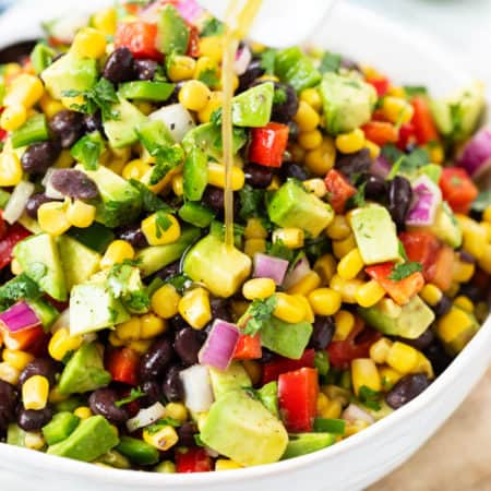 A white bowl filled with cowboy caviar with dressing being drizzled on top.