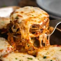 Eggplant Parmesan being pulled up from a casserole dish with hot mozzarella cheese on top.