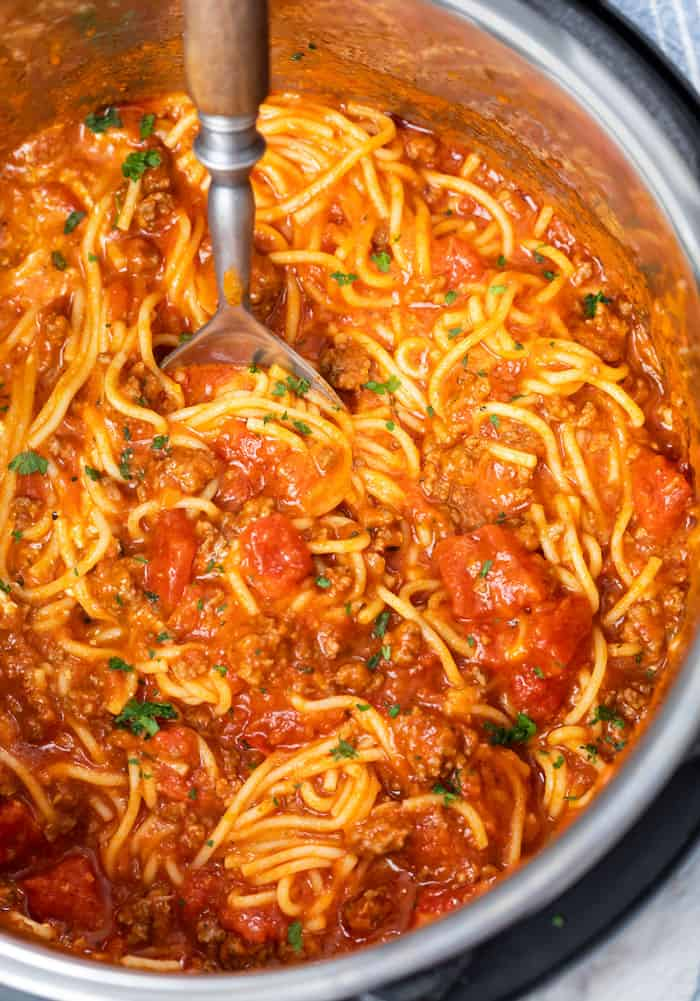 An Instant Pot filled with Spaghetti in marinara sauce with ground beef and diced tomatoes.
