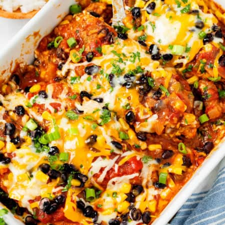 A casserole dish filled with Baked Salsa Chicken topped with melted cheese, cilantro, and green onions.