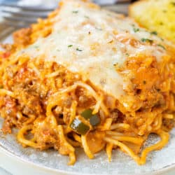 A plate with a slice of baked spaghetti topped with mozzarella cheese and a fork in the background.