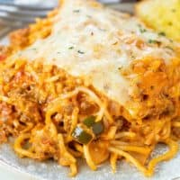Baked spaghetti topped with melted mozzarella cheese on a plate.