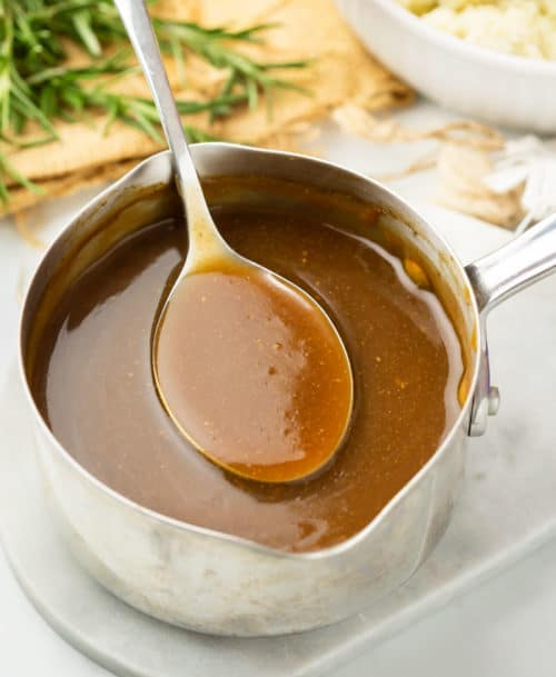 A pot of brown gravy with a spoon scooping it out with rosemary and mashed potatoes in the background.